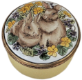 "Two Bunnies (Crummles) 1.25"" diameter. Soft Yellow base with two bunnies on the lid."
